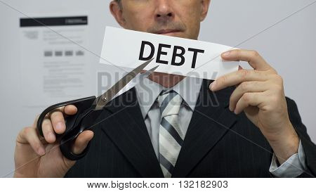 Male office worker or businessman in a suit and tie cuts a piece of paper with the word debts on it as a debt reduction business concept.