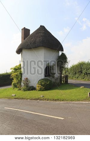 Hexagonal two-storey thatched toll house built around 1793 and served as a toll house when turnpikes were in use.A pouch hung on a hook over the door was used by coach drivers to pay the toll.