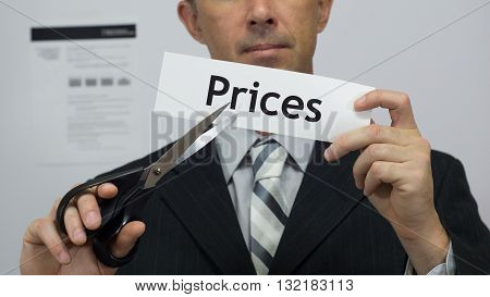 Male office worker or businessman in a suit and tie cuts a piece of paper with the word prices on it as a price reduction business concept.