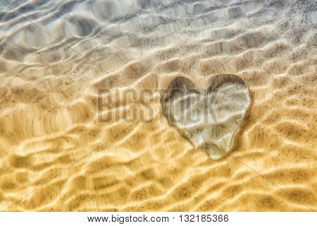 Rippled under water Heart distortion, blurred wave action over glass heart on beach