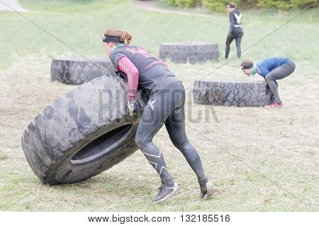 STOCKHOLM SWEDEN - MAY 14 2016: Man and woman struggling to tip a large tractor tire obstacle in the obstacle race Tough Viking Event in Sweden April 14 2016