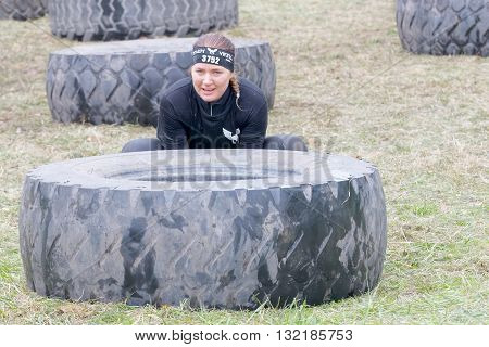 STOCKHOLM SWEDEN - MAY 14 2016: Woman struggling to tip a large tractor tire obstacle in the obstacle race Tough Viking Event in Sweden April 14 2016