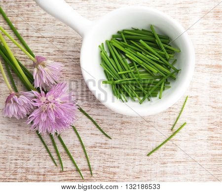 colorful summer chopped chives in a white dish with purple flowers window lit for soft focus wood grain background.