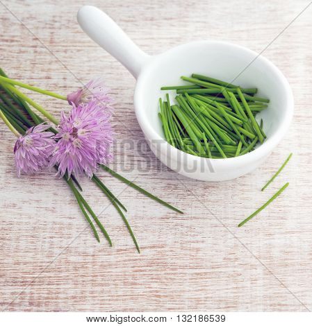 Bright overhead home grown chopped chives in a white dish with purple flowers window lit for soft focus wood grain background.