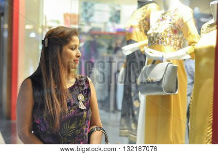 Woman eyeing Indian suits in clothing shop