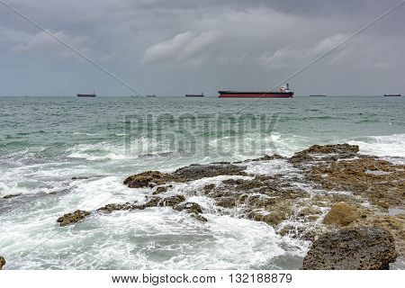 Ships anchored in the Bay of Todos os Santos in Salvador during bad weather waiting to moor in the harbor.