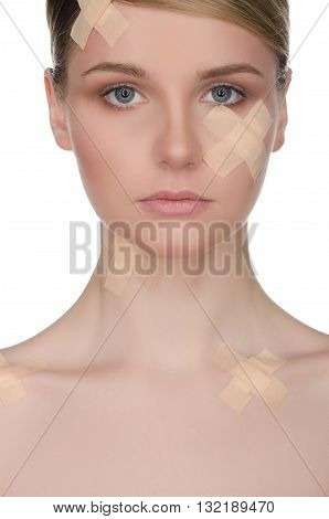 Ybeautiful woman with medical plaster on her face isolated on white