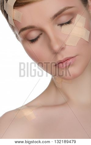 portrait of woman with medical plaster on her face isolated on white