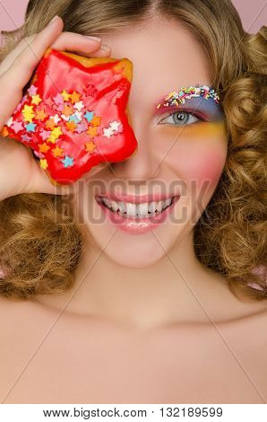Young woman with donut in face on pink background