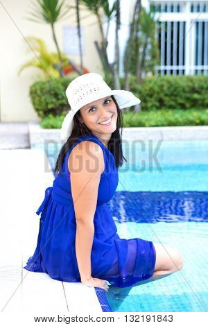 Beautiful hispanic woman in blue dress by the swimming pool