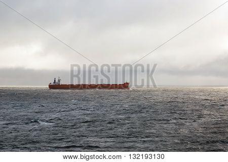 Red merchant cargo ship steaming through the ocean