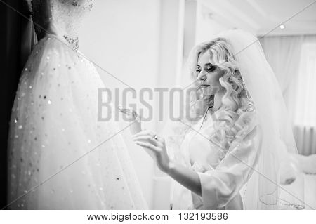 Young Beautiful Blonde Bride Looking At Her Wedding Dress