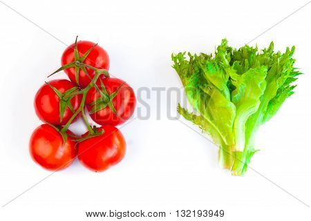 Fresh and ripe red tomatoes on the one brush and leaves of salad frillis on a white background
