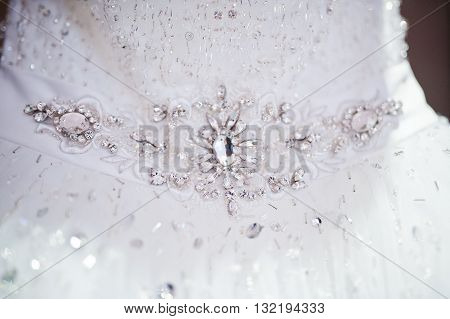 Diamond brooch at luxury wedding dress close up