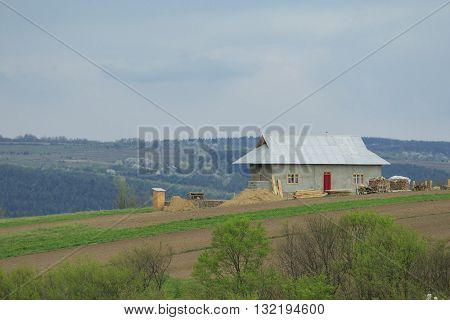 House under construction with building materials and garden on the top of the hill