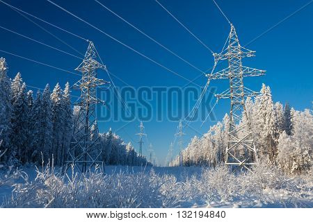 The group of high-voltage electricity power pylons over blue sky and covered by snow