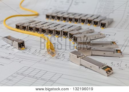 Electric gigabit sfp modules for network switch on the blueprint of  communication equipment and yellow patch cord