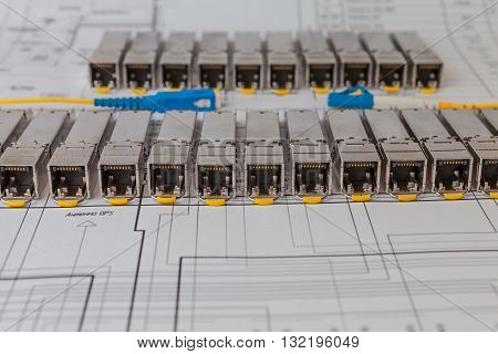 Electric gigabit sfp modules for network switch on the blueprint of  communication equipment and yellow optic patch cords