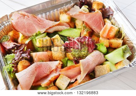 Healthy lunch. Natural organic food. Weight loss diet, low carb food take away in aluminium boxes. Healthy food background. Vegetable salad with crouton and ham closeup at white wooden table