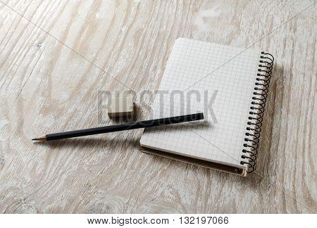 Blank sketchbook with a pencil and eraser on light wooden table background. Blank mock-up for design portfolios.