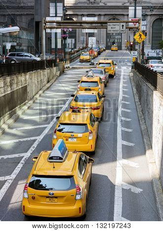 NEW YORK CITY, USA - May 28, 2016: Yellow taxi cabs in New York City wait outside Grand Central Terminal on Park Avenue for customers