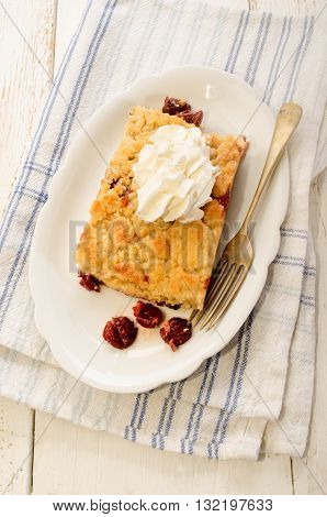 cherry crumble with whipped cream and fork on oval plate