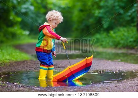 Little boy playing in rainy summer park. Child with colorful rainbow umbrella waterproof coat and boots jumping in puddle and mud in the rain. Kid walking in autumn shower. Outdoor fun by any weather