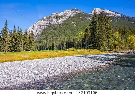 Autumn sunny day in the Canadian Rockies.  Dry creek in a mountain valley Banff park