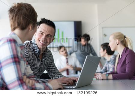young startup  business people, couple working on laptop computer,  businesspeople group on meeting in background at office interior