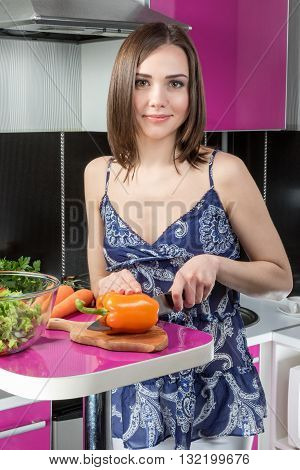 Beautiful woman standing at the table in the kitchen with a large knife cut the bell pepper laying on a cutting board