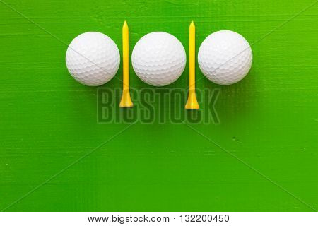 Golf balls and wooden golf tees on the wooden green table