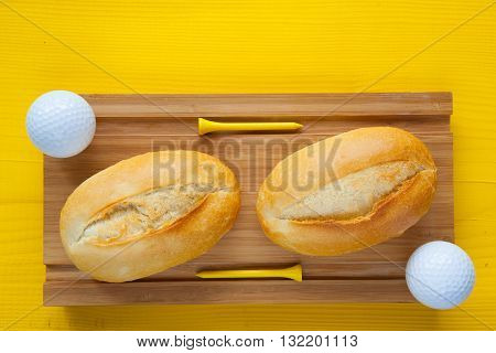 Golf breakfast - Two wheat bread and golf balls on wooden desk