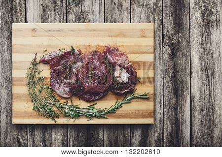 Fresh beef steak ready for BBQ cooking. Raw meat on a cutting board with rosemary leaf top view at rustic wood. Raw beef, veal meat on wood, closeup. Marinated in spices raw steak for barbecue.