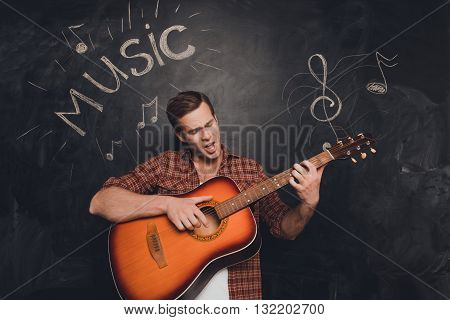 Handsome Man Playing On The Guitar And Singing On The Background Of Chalkboard