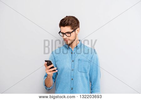 Portrait Of Young Guy In Spectacles Reading Message On Phone
