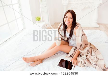 Smiling Woman Siting With Tablet And Basking With Tea And Plaid