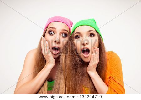 Two Surprised Girls With Open Mouth Touching Their Faces