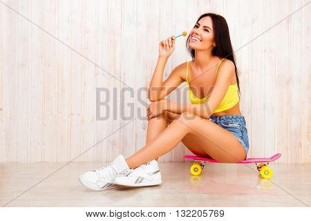 Pretty Girl Siting On Skate Bord And Licking Lollipop