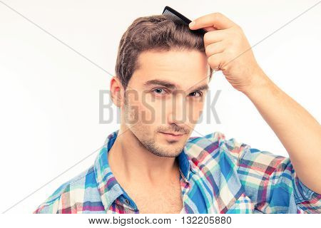 Handsome young man combing his hair  on a white background
