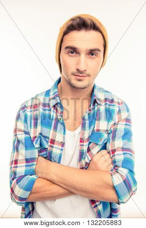 Handsome man with hat crossing hands  on a white background