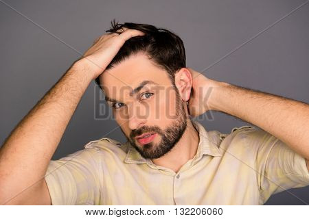Handsome young man combing his hair with fingers