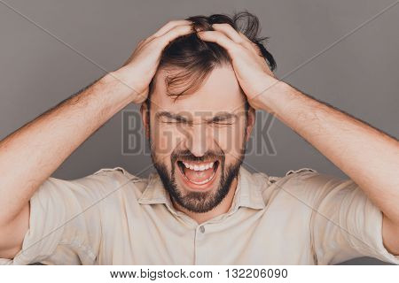 Portrait Of Nervous Depressed Man Touching Hair And Screaming