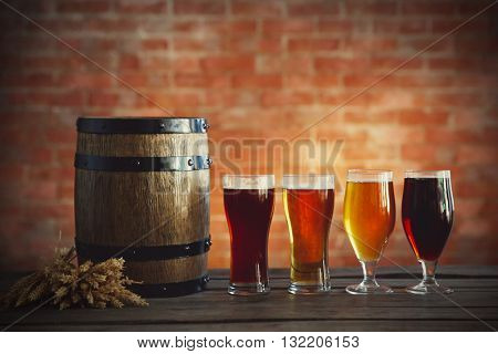 Glasses with different sorts of craft beer, wooden barrel and barley. Retro stylization