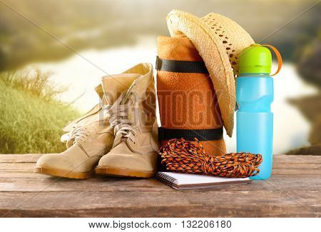 Tourism concept. Rug and plastic thermos on blurred nature background