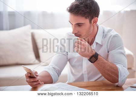 Deserve some rest.    Pleasant serious handsome man sitting at the table and holding cell phone while drinking coffee