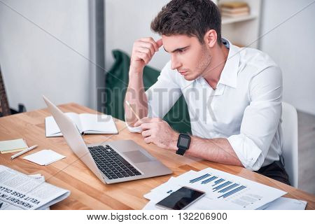 Diligent worker. Pleasant handsome concentrated man sitting at the table and working on the laptop while being involved in work