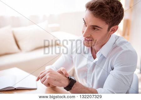 Positivity in mind. Pleasant cheerful handsome man sitting at the  table and using his smart watch while sitting at the table