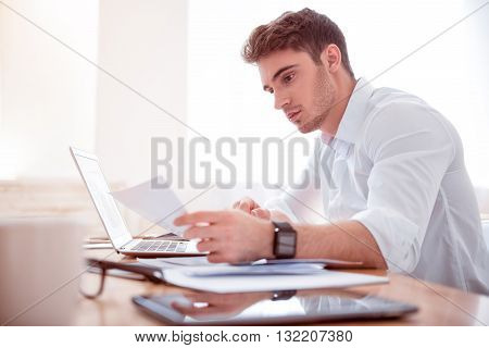 Multitasking in mind. Pleasant serious concentrated man sitting at the table and working with papers while sitting at the table