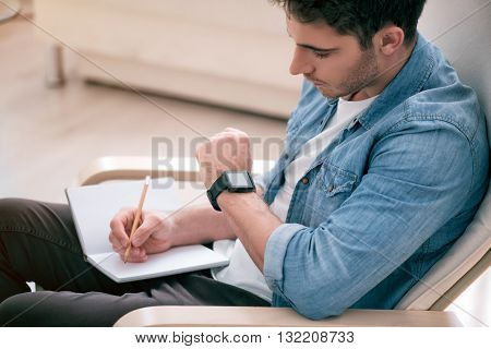Put it down, Pleasant handsome man sitting in the armchair and looking at his wrist watch while making notes