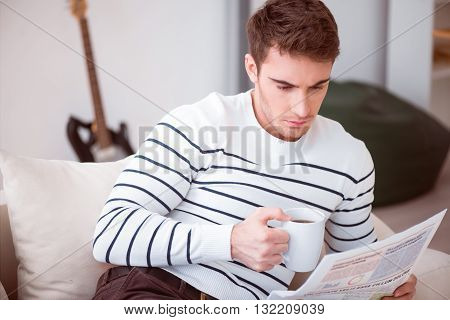 Deserved rest. Pleasant handsome concentrated man sitting on the couch and drinking coffee while reading newspaper